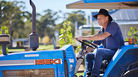 Photo of male farm worker on a blue tractor.