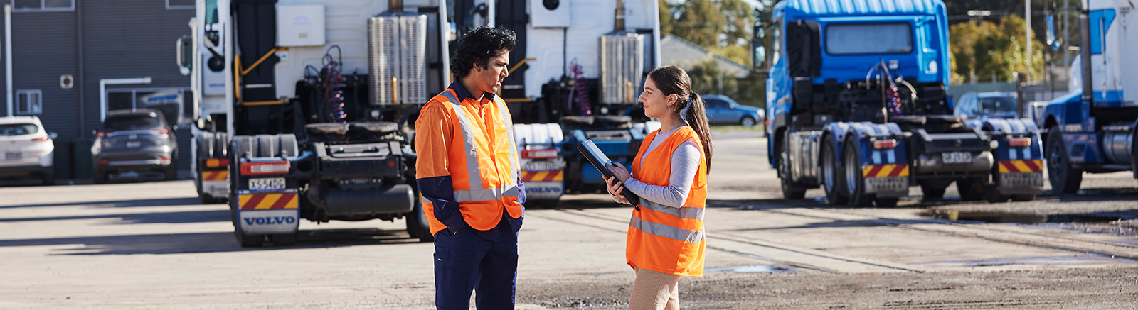 Male worker and female case manager talking on truck transport site